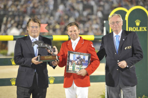 Christian Baillet, Chairman of the Jumping Owners Club, and FEI First Vice President Sven Holmberg present the award to Eric Lamaze. Photo by FEI/Kit Houghton